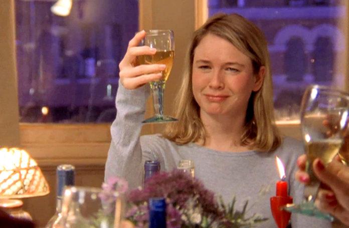 Blondwłosa kobieta w niebieskim swetrze z kieliszkiem w dłoni