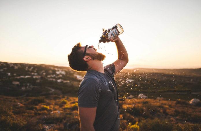 Mężczyzna na pustyni pijący z butelki jakiś trunek, w tle rozciąga się pustynia