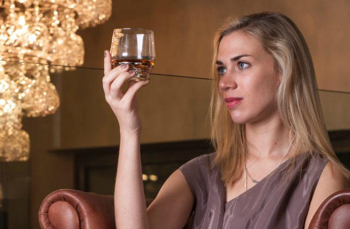 Blondynka trzymająca na wysokości oczu szklankę z whiskey