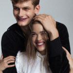 Roześmiana dziewczna i chłopak trzymający rękę na jej głowie