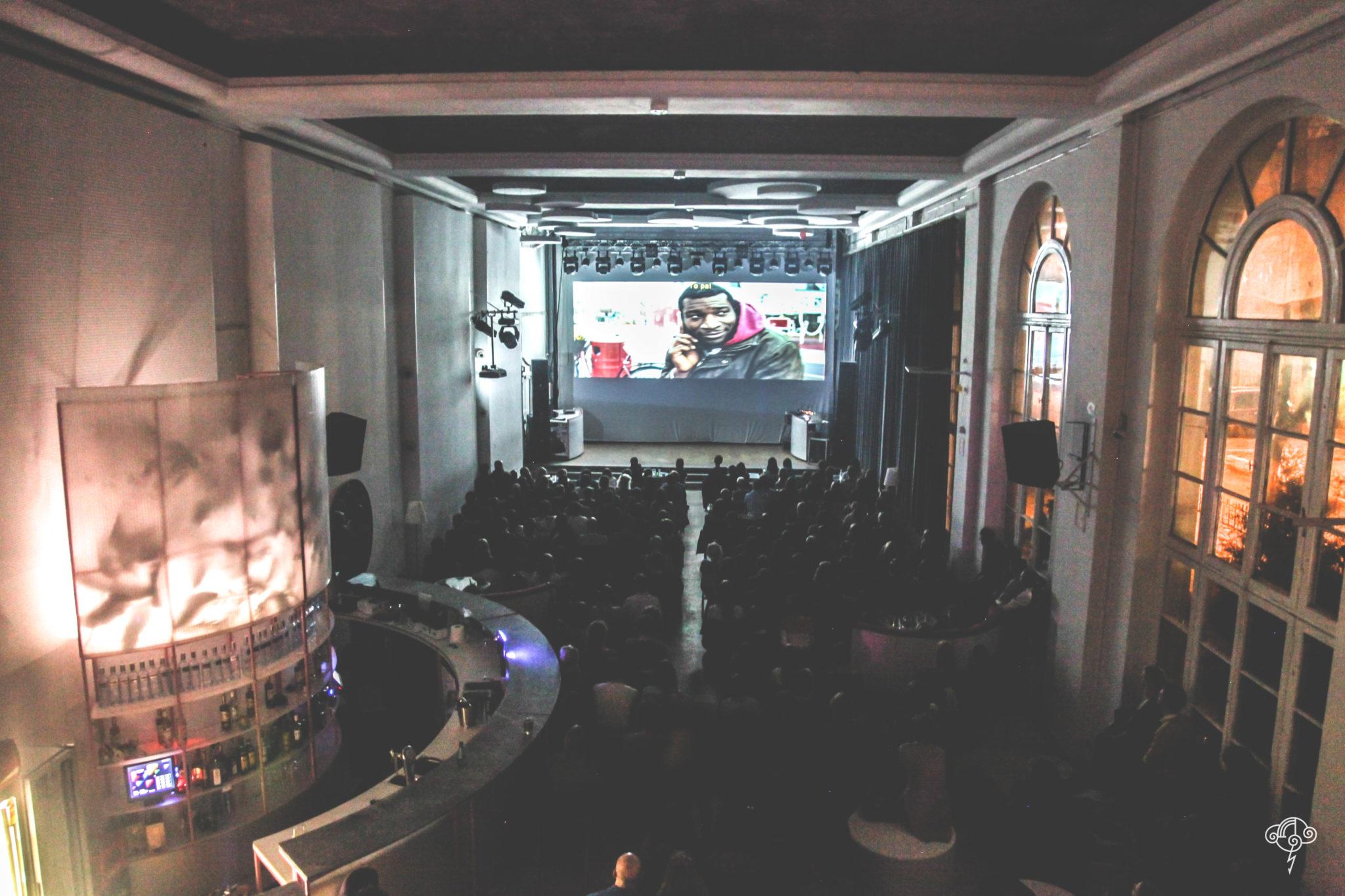 Duża sala z ekranem na którym wyświetlany jest film