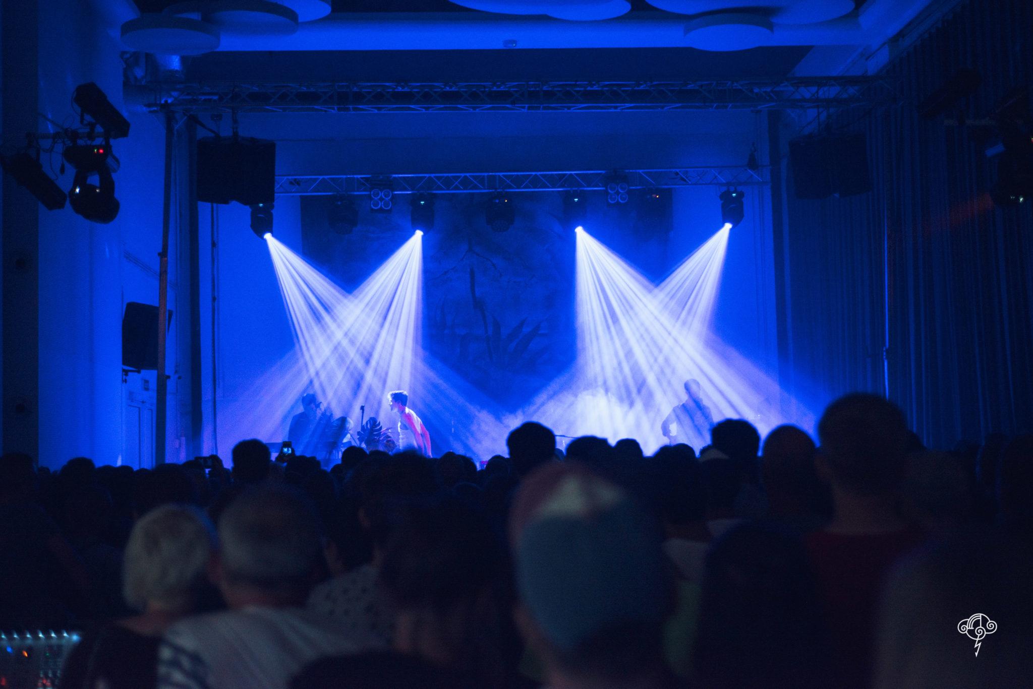 Oświetlona reflektorami scena i tłum ludzi