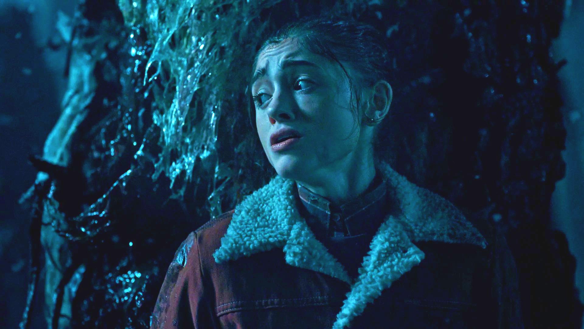 Młoda dziewczyna ukrywa się przy drzewie, który jest cały w śluzie.
