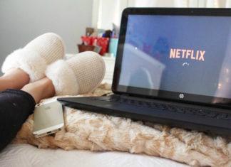 Laptop z włączonym Netflixem, kobiece nogi i telefon