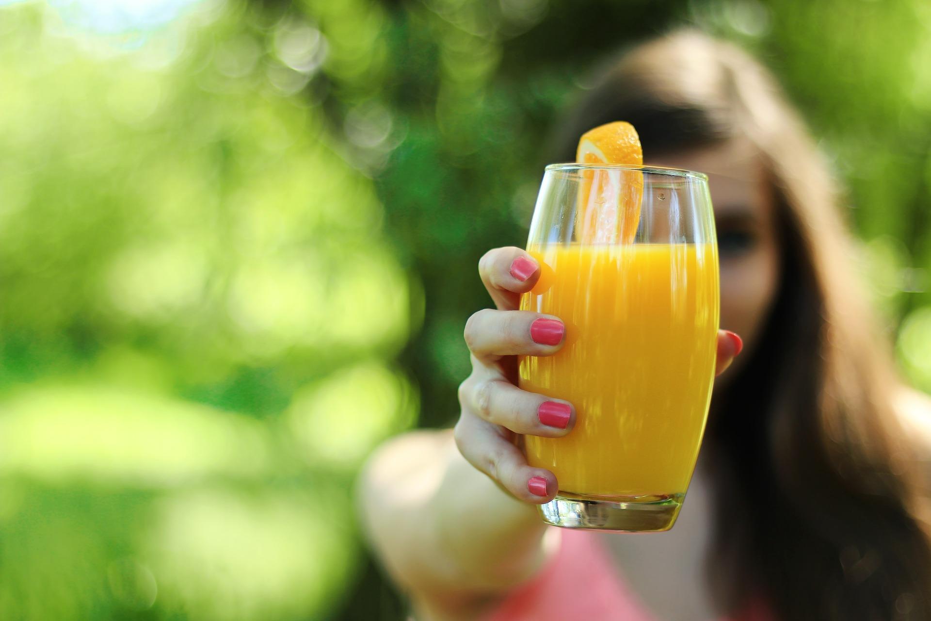 Kobieta trzymająća w wyprostowanej ręce przed sobą szklankę soku pomarańczowego