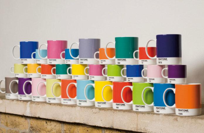 Dużo kubków Pantone ustawionych na szafce