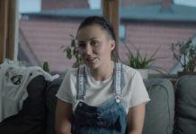 Dziewczyna siedząca na kanapie w ogrodniczkach i białej bluzce