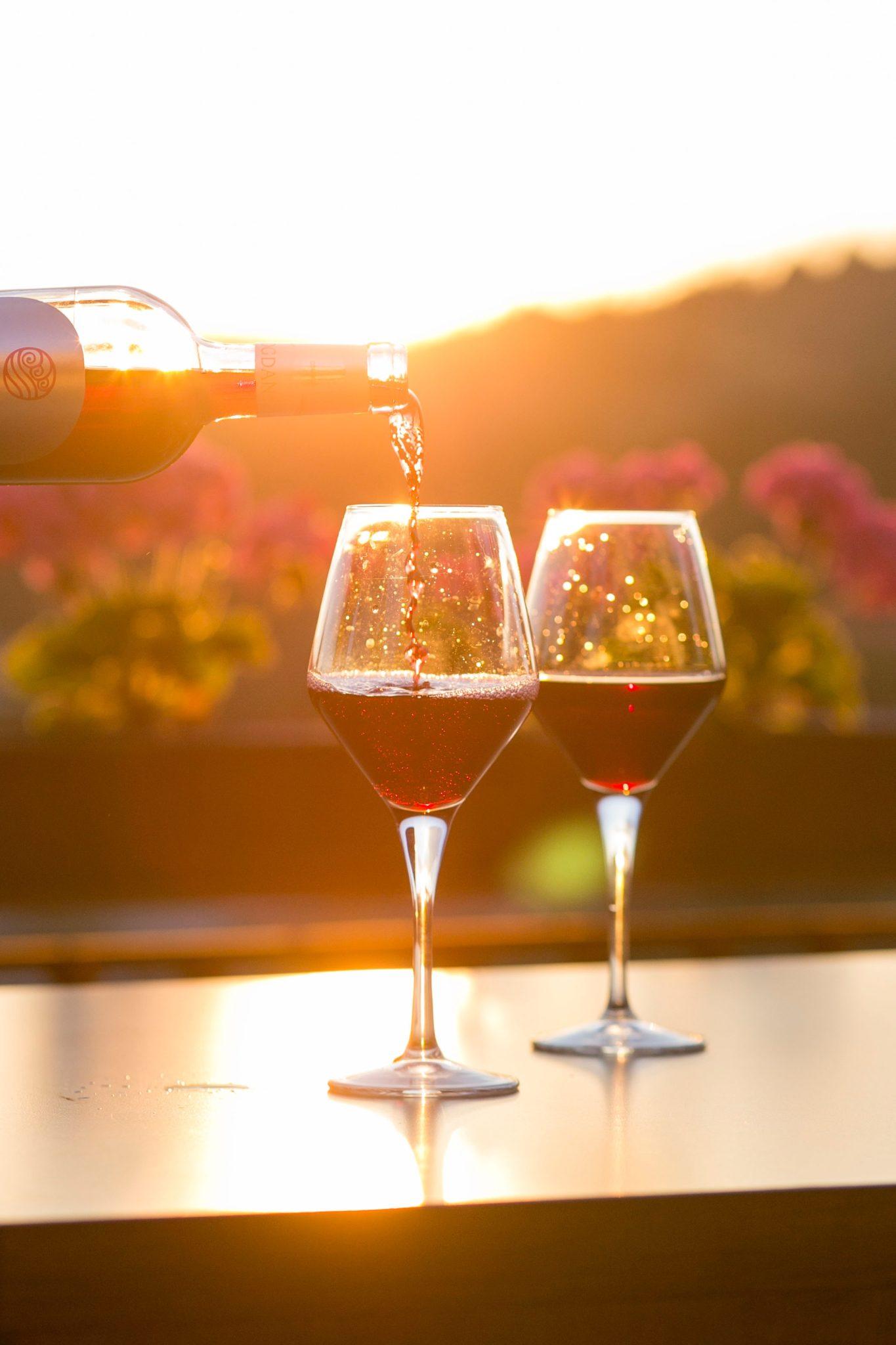 Dwie lampki czerwonego wina stojące na stole, a w tle ogród o zachodzie słońca