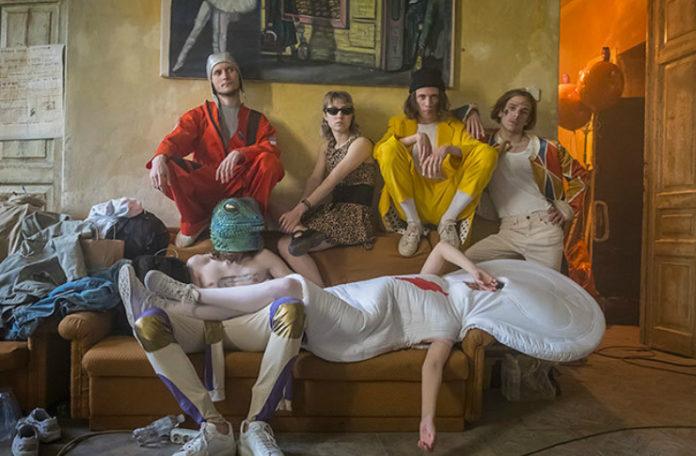 Grupka ludzi i ktoś leżący na kanapie, przebrany za zakrwawioną podpaskę