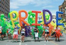 Ludzie stojący z napisem PRIDE zrobionym z balonów