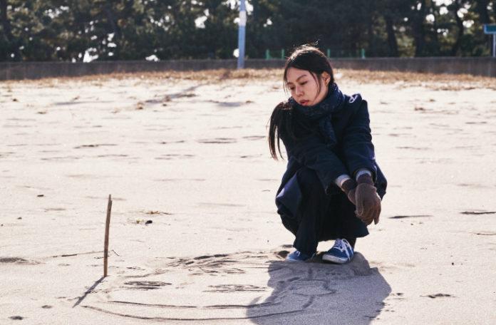 Dziewczyna kucająca na plaży