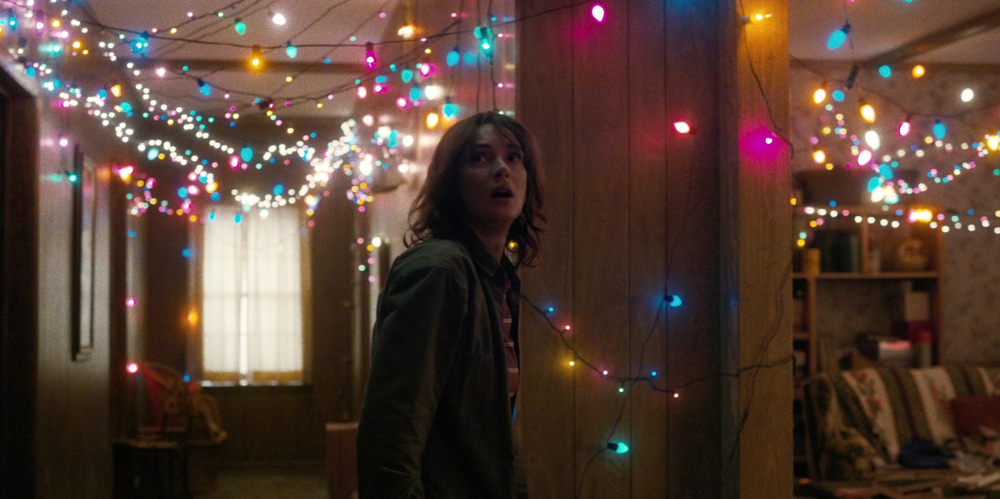 Kobieta stoi w pokoju, w którym wszędzie są powieszane małe lampki na łańcuszkach.