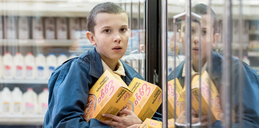 Dziewczynka trzyma pudełka z ciasteczkami przy lodówkach w sklepie.