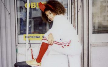 Analogowe zdjęcie przedstawiające dziewczynę z afro na głowie ubraną w biały dres, czerwone skarpetki i złote buty