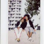 Dwie ciemnoskóre dziewczyny siedzące na murku przy blokowisku