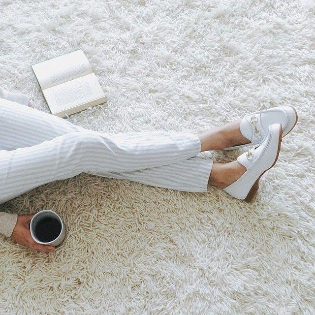 Dziewczyna ubrana w białe spodnie, siedząca na białyym dywanie z kubkiem kawy