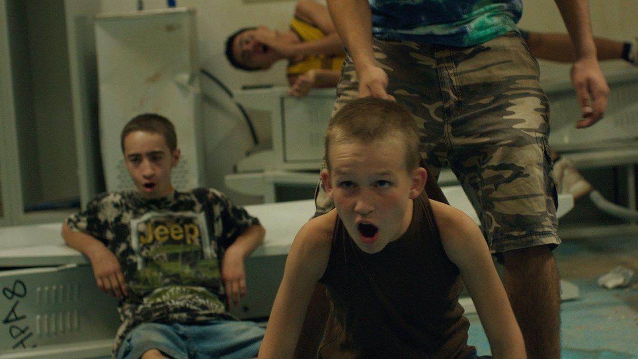 Dwójka chłopców krzyczy patrząc w ekran telewizora.