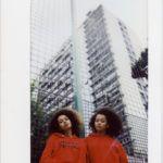 Dwie ciemnoskóre dziewczyny ubrane w czerwone blizy, na tle ogrodzenia z siatki