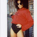 Ciemnoskóra dziewczyna stojąca na tle siatki od ogrodzenia, ubrana w czerwoną bluzę i czarne majtki