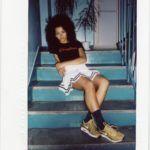 Ciemnoskóra dziewczyna siedząca na turkusowych schodach w czarnej koszulce i białej spódnicy