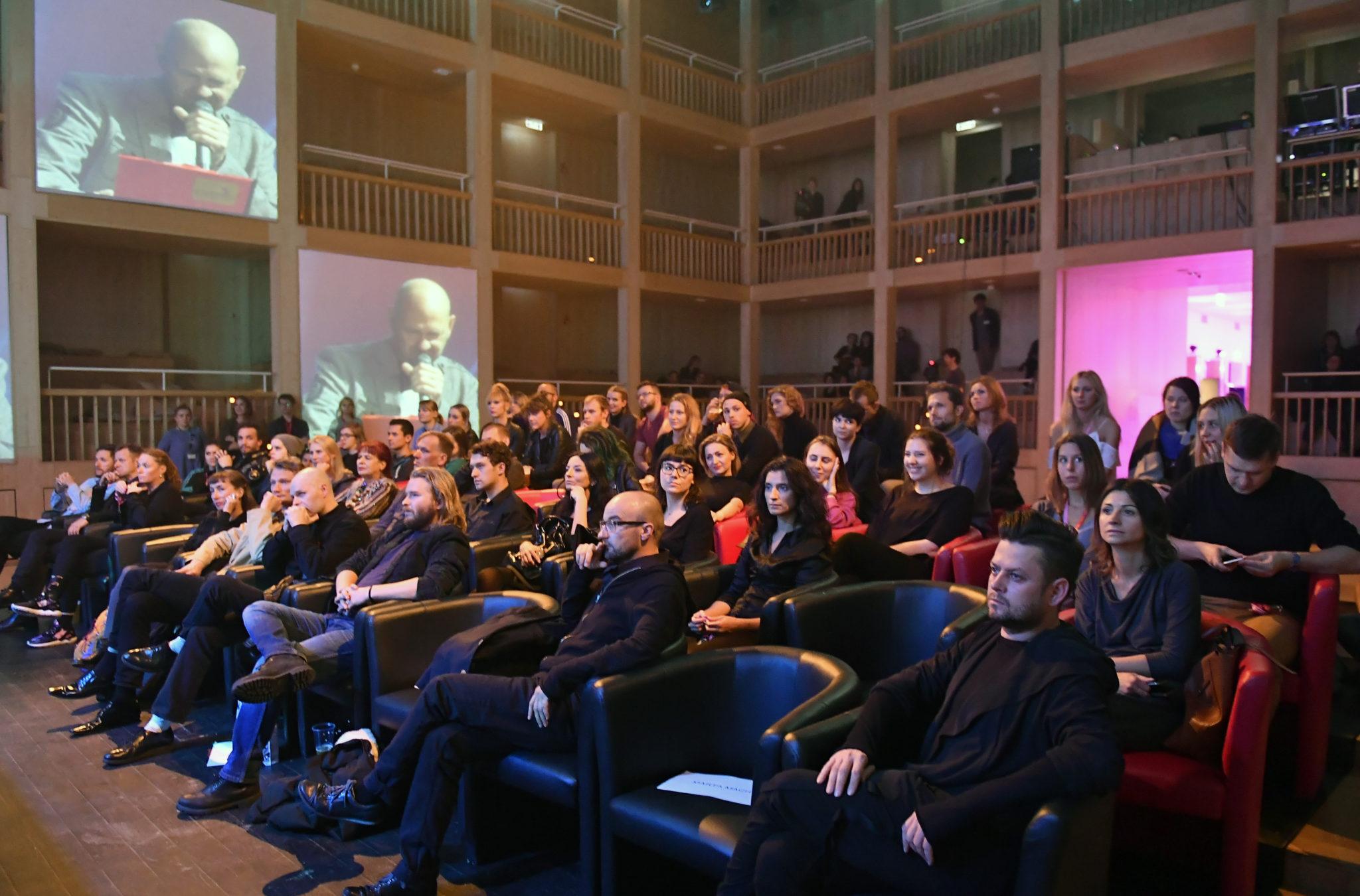 Sala wypełniona ludźmi siedzącymi na fotelach