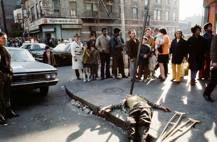 Człowiek leżący nieprzytomny na ulicy, dookoła stojący ludzie