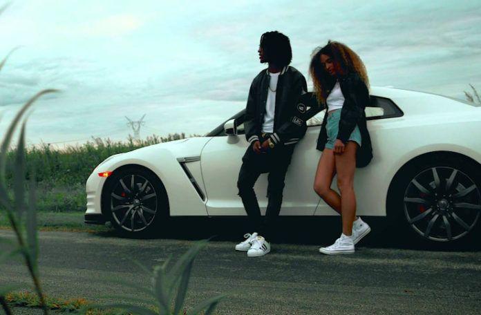 Czarnoskóry mężczyzna i kobieta stojący przy białym samochodzie