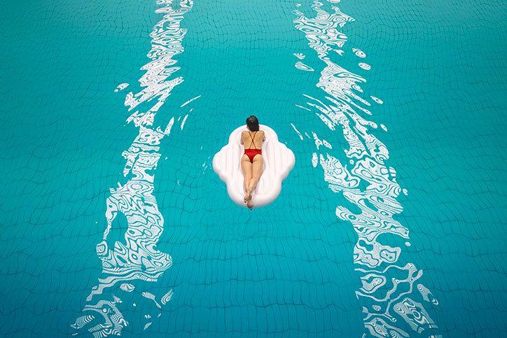 Kobieta pływająca na dmuchanym materacu w basenie.