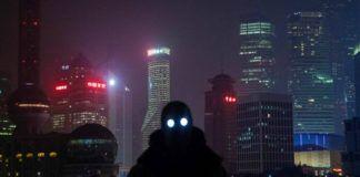 Mężczyzna w czarnej kominiarce, ze świecącymi oczami, na tle miasta nocą