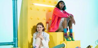 Dwoje ludzi siedzących na żółtej platformie