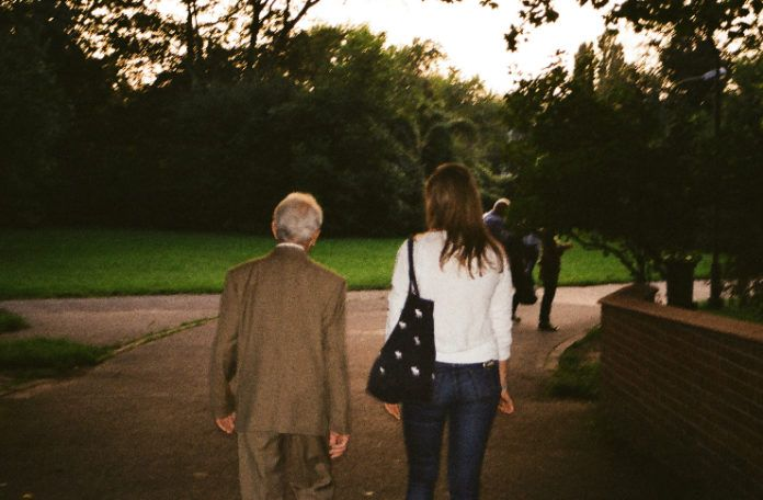 Starszy pan wraz z młodą kobieta idą drogą.