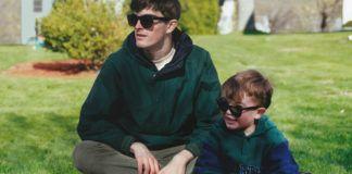 Chłopiec i mężczyzna siedzą w zielonych bluzach i okularach na trawie