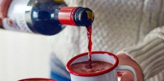 Dłoń trzymająca kubek z czekoladą, dolewająca do niego wina