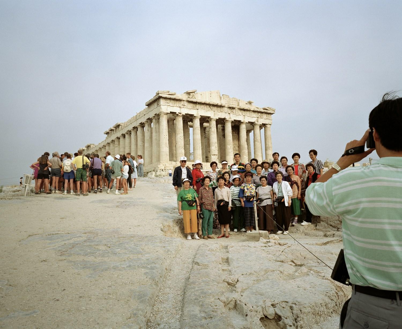 Zdjęcie mężczyzny robiącego zdjęcie grupie turystów na tle zabytku.