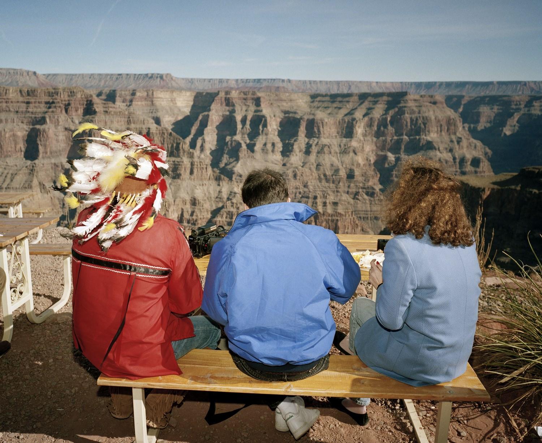 Zdjęcie trójki ludzi, którzy siedzą na ławce i patrzą się na krajobraz gór.