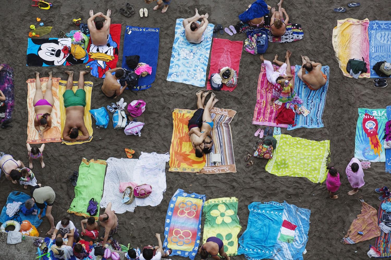 Zdjęcie plaży, gdzie ludzie leżą na ręcznikach.