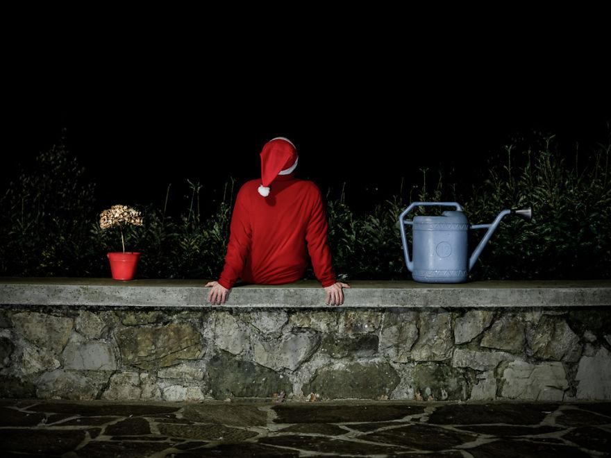 Mężczyzna w czerwonej koszuli i czapce opiera się o mur.