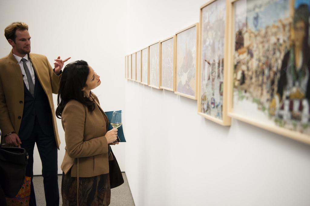 Kobieta i mężczyzna patrzą się na ścianę, na której są powieszone obrazy.