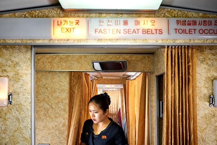 Wnętrze samolotu i wychodzącca zza zasłony kobieta