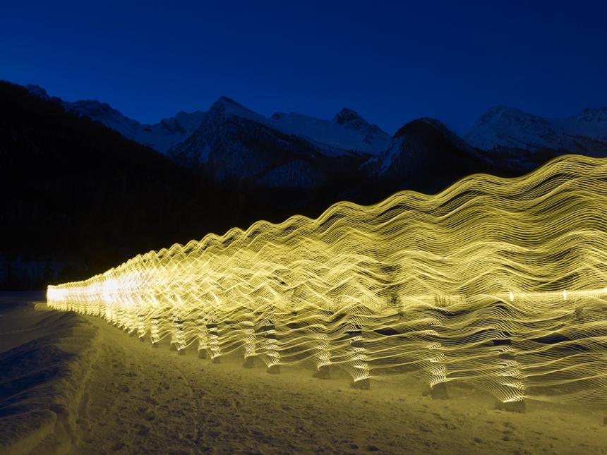 Osoba w stroju LED-owym porusza się, lecz zdjęcie jest z długim czasem naświetlania, co powoduje smugi światła