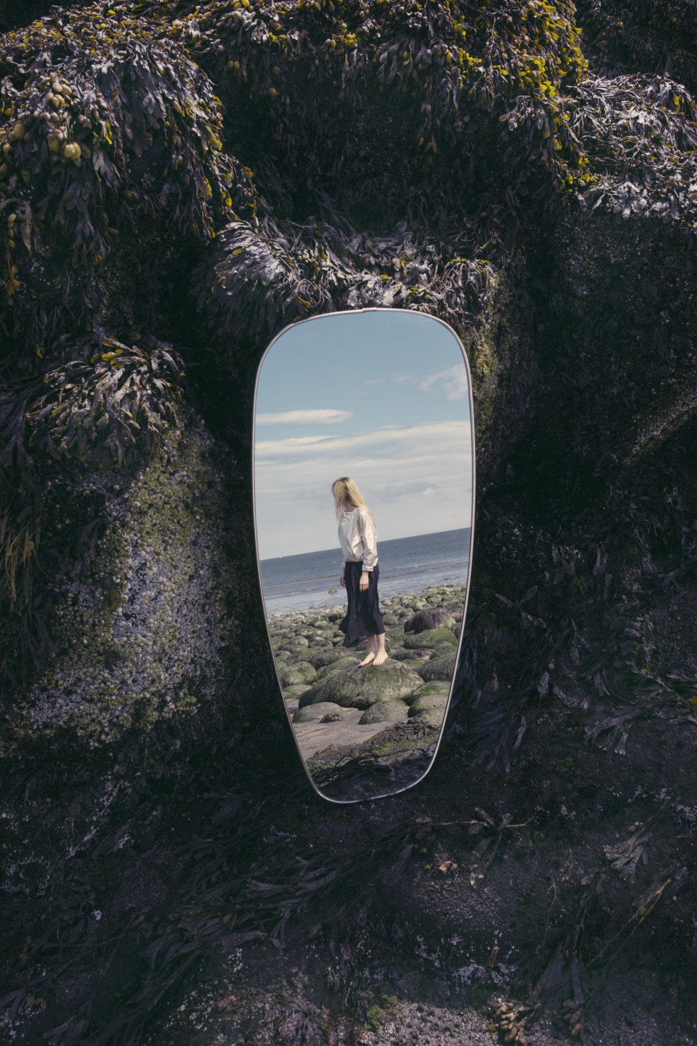 Zdjęcie w zdjęciu. Na samym środku jest lustro, a w nim odbicie plaży wraz ze stojącą kobietą.