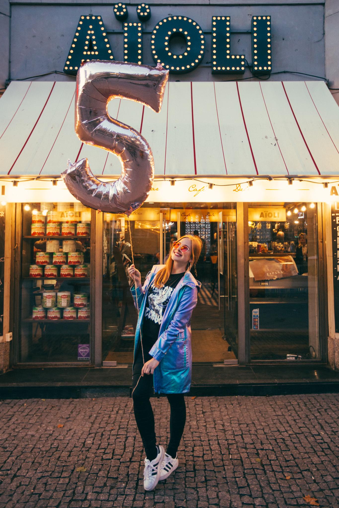 """Dziewczyna stojąca przed restauracją z balonem """"5"""""""