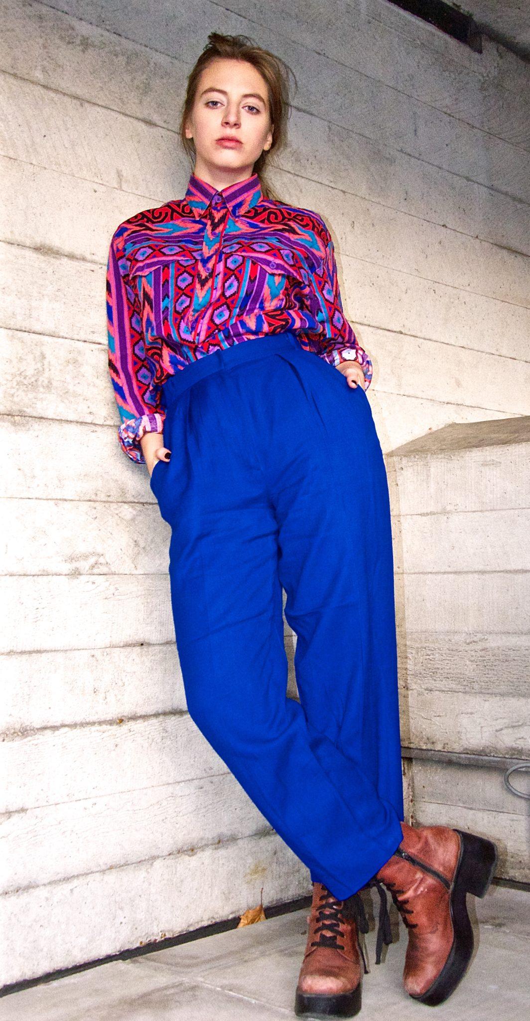Dziewyczna stojąca pod ścianą ubrana w kolorową bluzkę