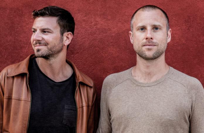 Dwóch mężczyzn na tle czerwonej ściany