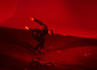 Mężczyzna pochylający się na scenie w czerwonym świetle