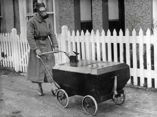 Matka z maską gazową prowadzi dziecko w opancerzonym wózku.