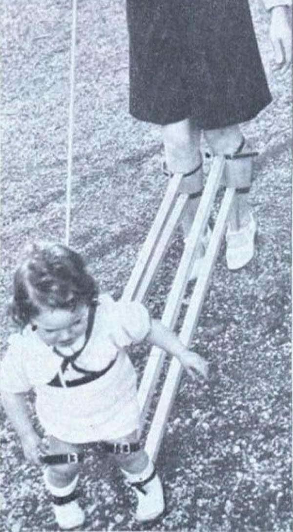 Płaczące dziecko jest trzymane za nogi drewnianym narzędziem.