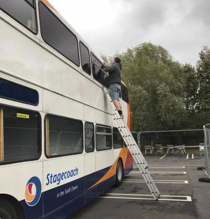 Męzczyzna na drabinie opartej o bus