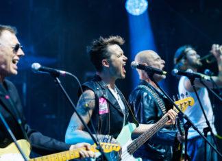 Trzech muzyków grających na gitarach w trakcie koncertu