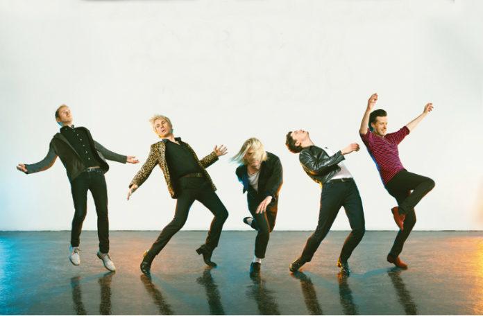 Grupa mężczyzn stojąca w jednej linii na tle białej ściany